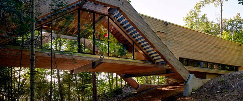 Una casa de madera se extiende como un puente en un for Casa con piscina quebrada alvarado