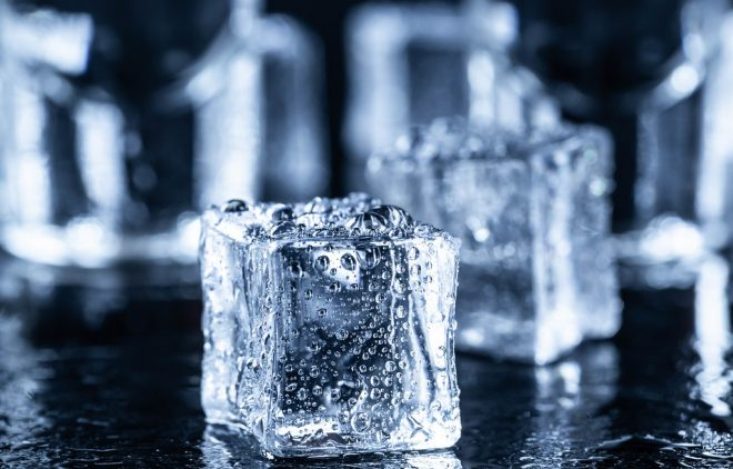 Ice cubes with water drops and vodka glasses in the background